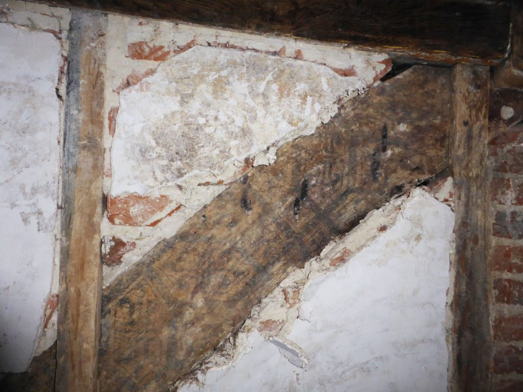 Painted brace in stairwell, before conservation